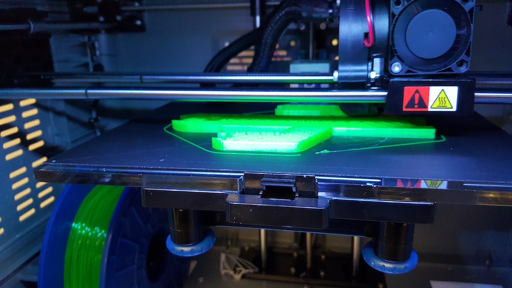 A 3D printer in the middle of printing a neon green item
