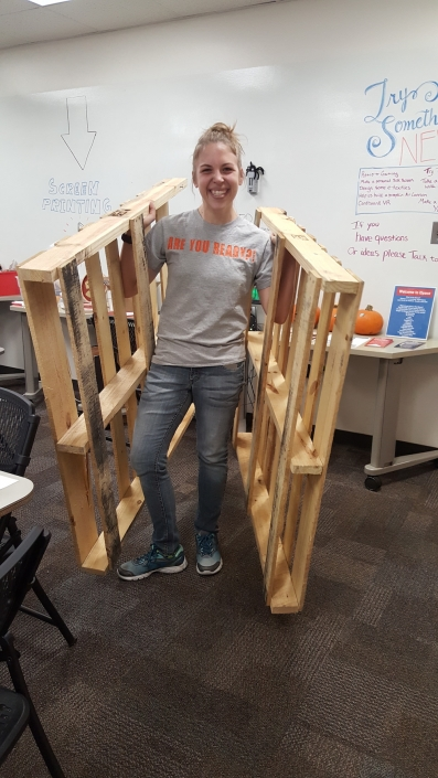 A person smiling while holding two wooden pallets