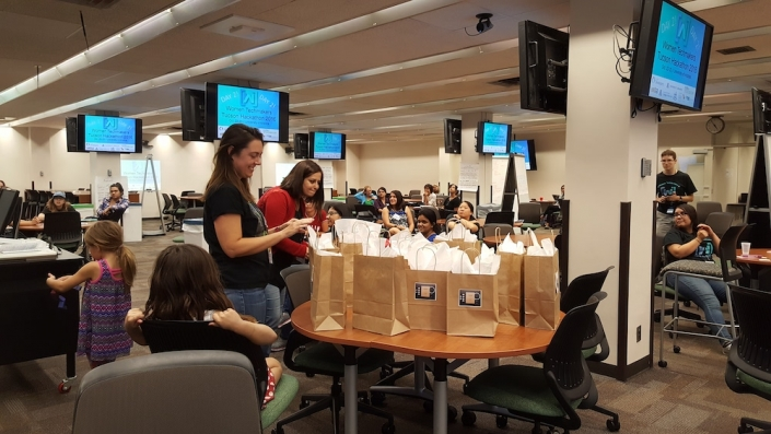 Two people looking over a table filled with gift bags at the UA Women's Hackathon