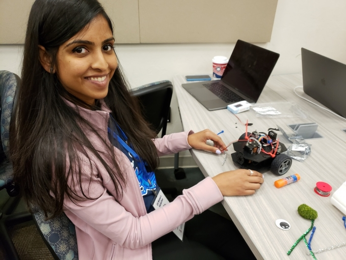 A person smiling while doing some tech work at the UA Women's Hackathon