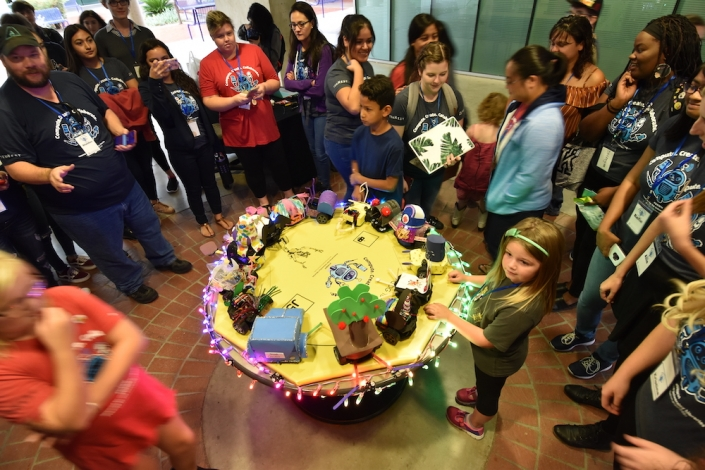 People surrounding a table with creative objects at the UA Women's Hackathon