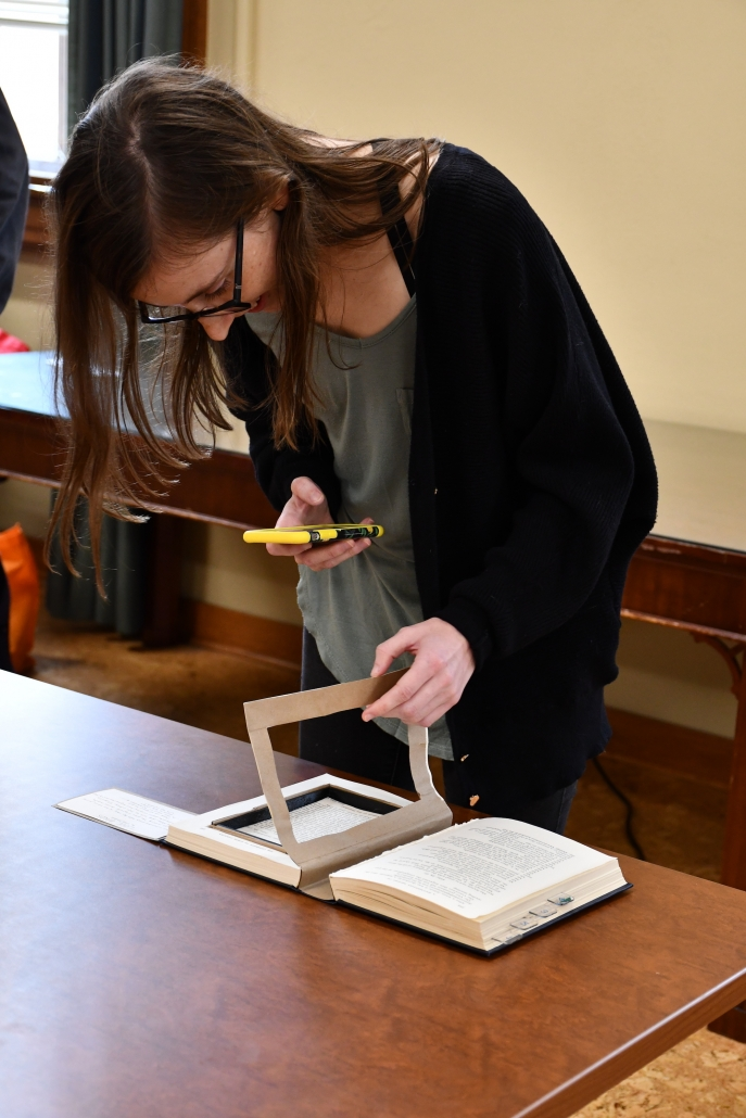 A woman using her phone to view an artifact's augmented reality as part of the Bibliocircuitry: Old Books, New Stories showcase