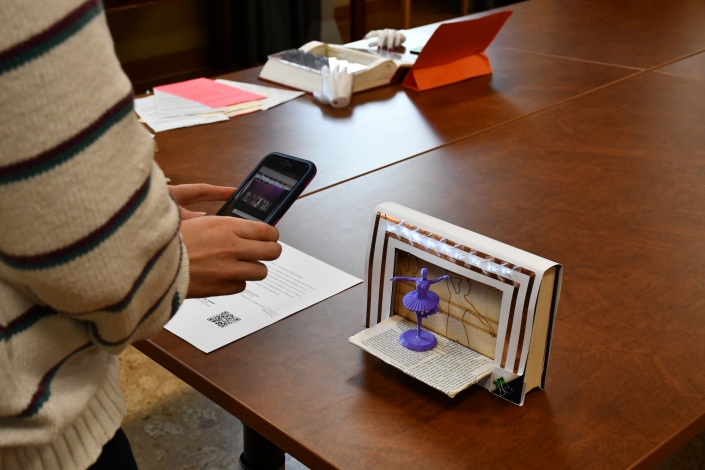 A person using their phone to see augmented reality as part of the Bibliocircuitry: Old Books, New Stories showcase