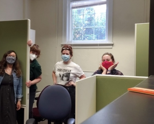 Maggie, Laura, Mimi, and Emily standing behind furniture in the new lab space